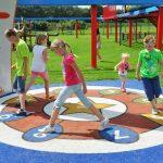 Savia proyectos juegos interactivos niños jugando sobre pavimento de seguridad en parque infantil con números en el suelo bajo arco