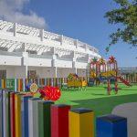 Savia proyectos parque infantil en pavimento de seguridad con balancines pasarelas y toboganes en hotel vista sobre valla multicolor