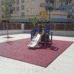 Savia proyectos parque infantil azul y amarillo sobre pavimento de seguridad frente a edificios vista frontal