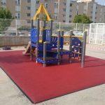 Savia proyectos parque infantil azul y amarillo sobre pavimento de seguridad frente a edificios
