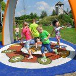 Savia proyectos parque infantil en césped juegos interactivos niños jugando sobre pavimento de seguridad con números en el suelo bajo arco