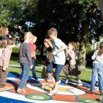 Savia proyectos juegos interactivos niños jugando sobre pavimento de seguridad con números en el suelo bajo arco