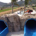 Savia proyectos parque acuático entrada toboganes azules en roca vista completa