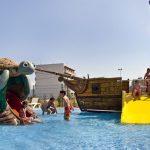 Savia proyectos piscina infantil con barco pirata con tobogán amarillo y tobogán con tortuga niños y adultos jugando en la piscina