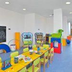 Savia proyectos interior miniclub con mesas y sillas verdes hojas con dibujos y lápices sobre la mesa pantalla táctil y pizarra con letras