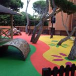 Savia proyectos suelo seguro con juego rayuela y mascota árboles y hojas pintadas en el suelo frente a caseta de madera
