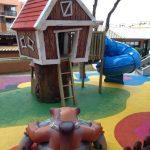Savia proyectos mundo de los sueños caseta con escaleras y tobogán azul sobre pavimento de seguridad y muñeco en el suelo