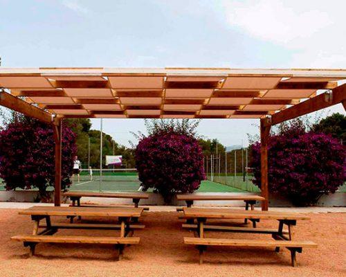 Savia proyectos pérgola sobre mesas de madera con bancos frente a cancha de tenis