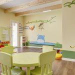 Savia proyectos miniclub infantil interior con mesas y sillas pequeñas y en la pared tigre e hipopótamo y reloj