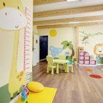 Savia proyectos miniclub infantil interior con mesas y sillas pequeñas y en la pared jirafa elefante león y palmera con cejas en el suelo
