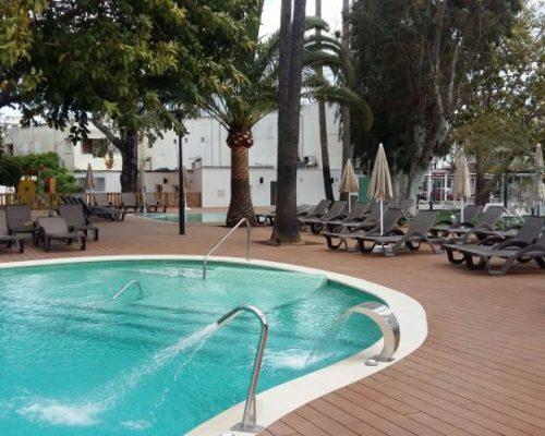 Savia proyectos tarima madera en piscina ovalada con hidromasaje y hamacas
