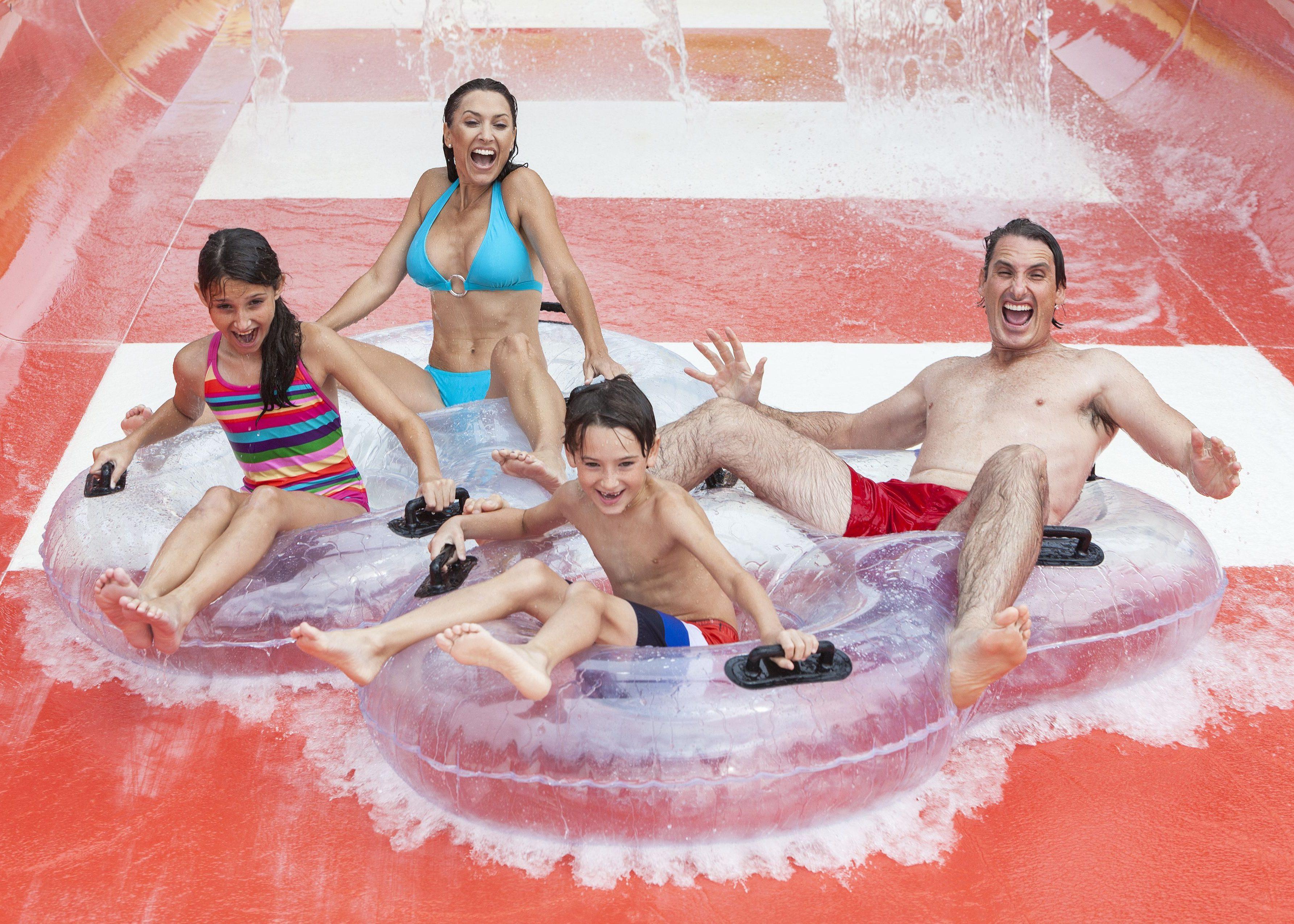 Savia proyectos familia tirándose por tobogán rojo y blanco con flotador