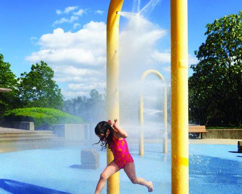 Little girl running through sprinkler in the summer