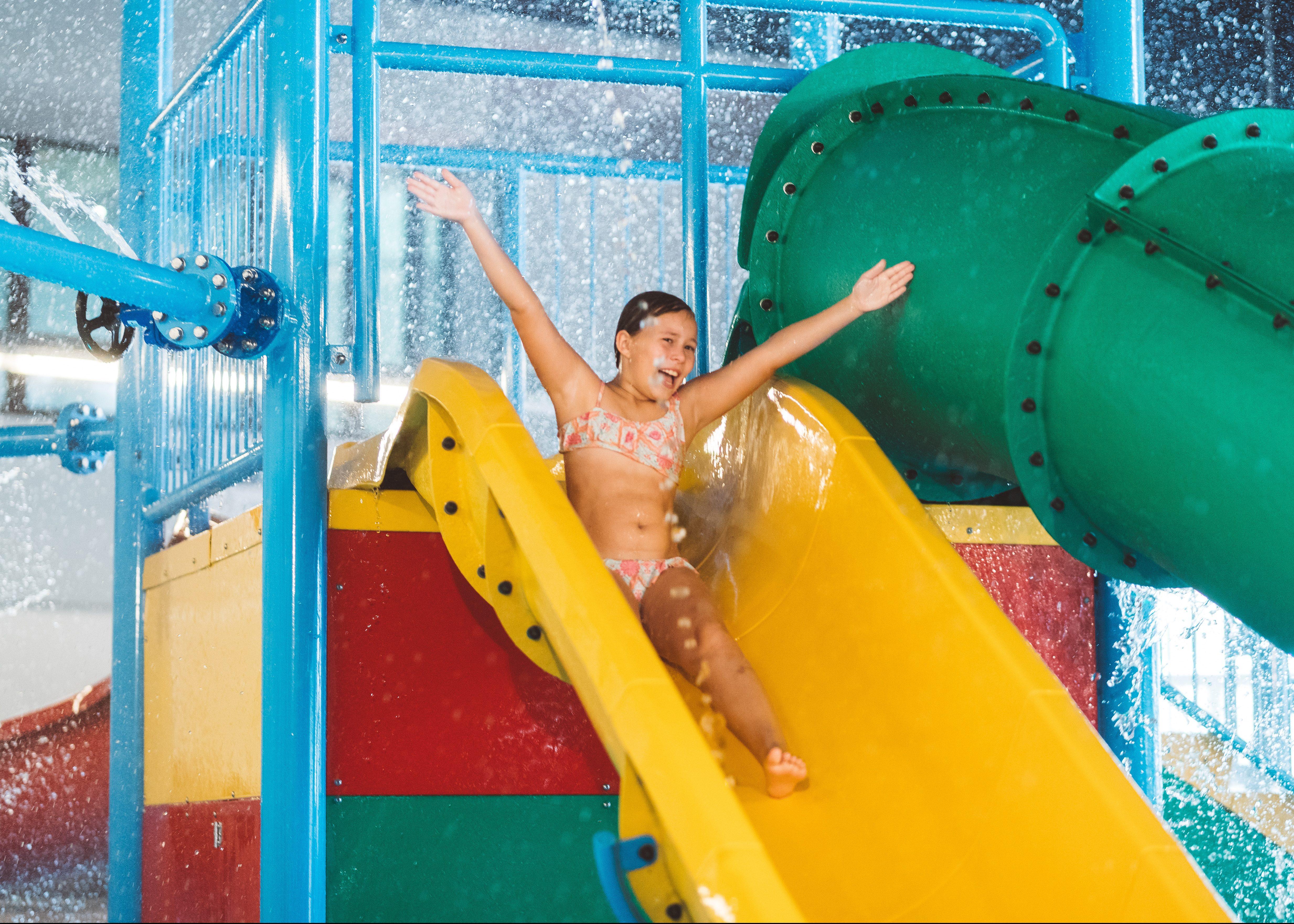 Savia proyectos parque acuático infantil interior niña tirándose por tobogán amarillo