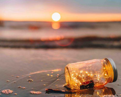 Savia puesta de sol y recipiente con luces en orilla del mar